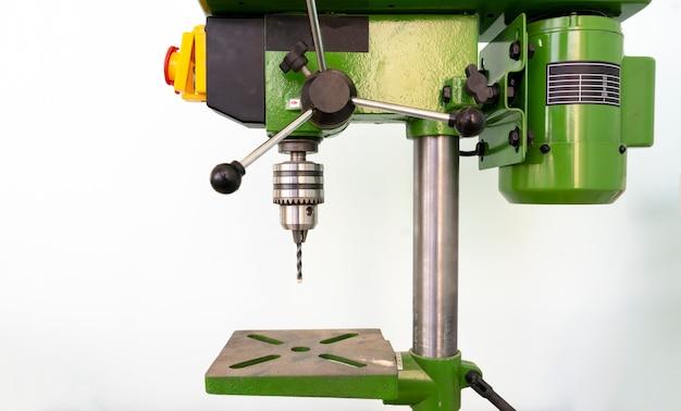 Eine stahltischbohrmaschine in der fabrik isoliert, arbeitsprozess