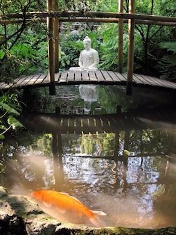 Eine statue von buddha, die in einem teich sitzt. ein roter fisch schwimmt im teich.
