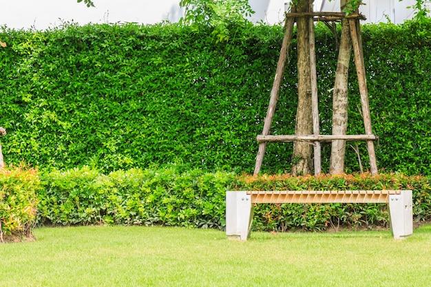 Eine steinbank unter einem baum mit naturhintergrund in einem garten.