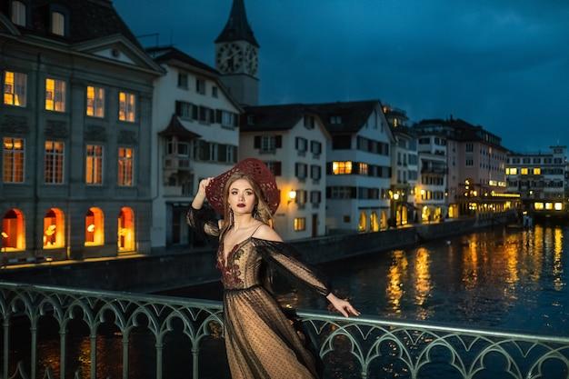 Eine stilvolle braut in einem schwarzen hochzeitskleid und einem roten hut posiert nachts in der altstadt von zürich. schweiz.