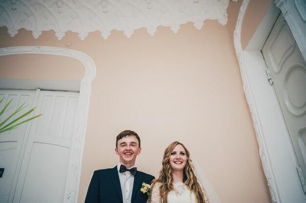 Eine stilvolle elegante braut und der bräutigam stehen auf dem hintergrund der wand, weiße türen.