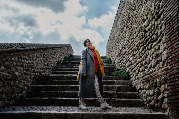 Eine stilvolle frau in einem mantel, der vor einer steintreppe aufwirft