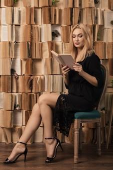 Eine stilvolle frau in einem schwarzen kleid liest das sitzen auf einem vintage-stuhl nahe der wand der bücher