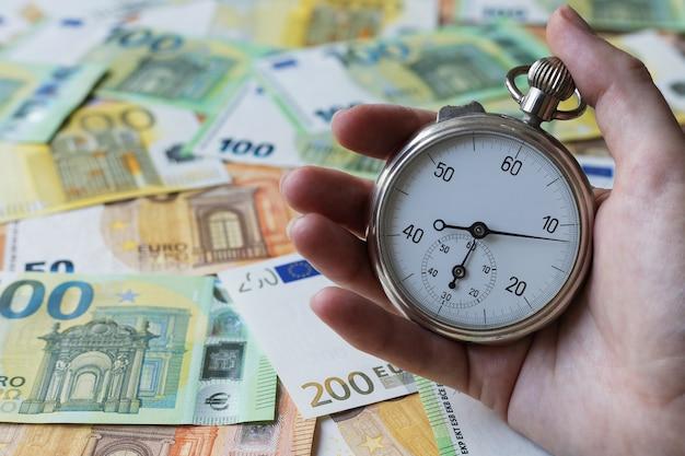 Eine stoppuhr in einer hand auf einem euro-banknotenhintergrund