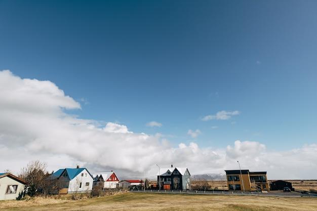 Eine straße mit wohnhäusern in einem schlafbereich in island, in der isländer vor blauem himmel leben