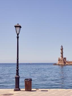 Eine straßenlaterne und ein leuchtturm im hafen von chania auf kreta mit einem blauen meer und himmel im hintergrund. speicherplatz kopieren.