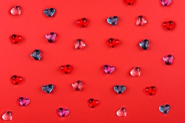 Eine streuung von farbigen glasherzen auf rotem hintergrund zum valentinstag.