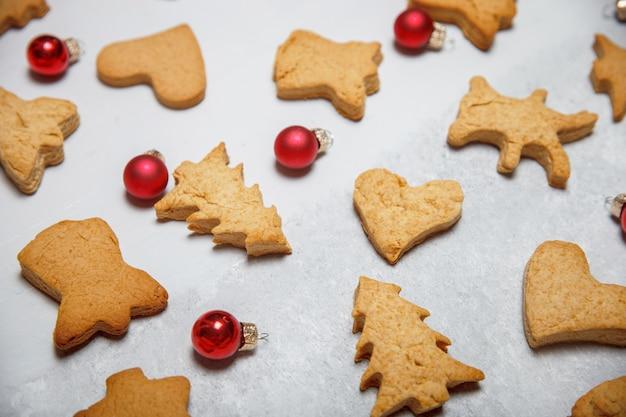 Eine streuung von weihnachtsplätzchen auf einer grauen oberfläche. flaches layout. draufsicht. weihnachts- und neujahrskonzept. kochen