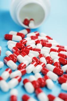 Eine streuung von weißen dosen mit roten und weißen ampullen mit medizin und vitaminen auf blauem grund. arzneimittel