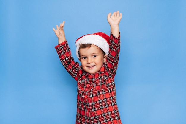Eine studioaufnahme eines glücklichen jungen im weihnachtspyjama, der herumalbert und lächelt. das konzept der ferien.