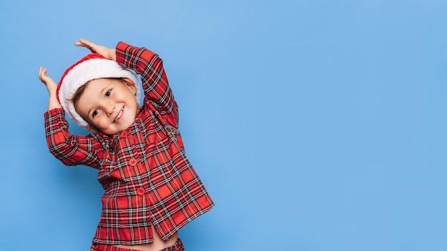 Eine studioaufnahme eines glücklichen jungen im weihnachtspyjama, der herumalbert und lächelt. ein platz für ihren text. das konzept der ferien.