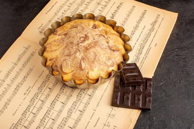 Eine süße ansicht des süßen runden kuchens der draufsicht innerhalb der kuchenform zusammen mit schokoriegeln auf dem grauen hintergrundkekszuckerplätzchen