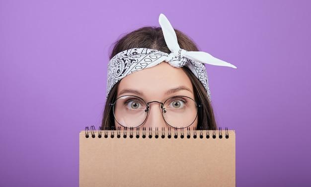 Eine süße braunhaarige frau mit runder brille versteckt ihr gesicht hinter einem notizbuch.
