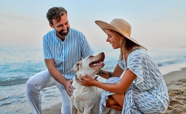 Eine süße frau in einem kleid und einem strohhut und ein gutaussehender mann in einem gestreiften hemd mit ihrem labrador-hund haben spaß an der küste.
