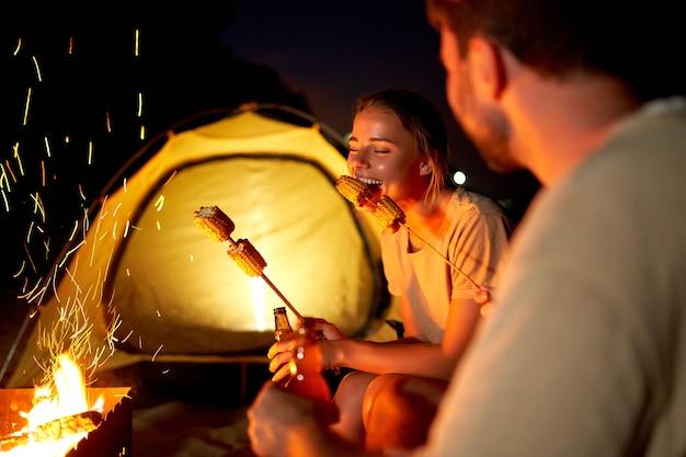 Eine süße frau und ein hübscher mann sitzen auf klappstühlen in der nähe des zeltes am feuer, trinken bier, essen mais und haben nachts spaß am strand am meer.
