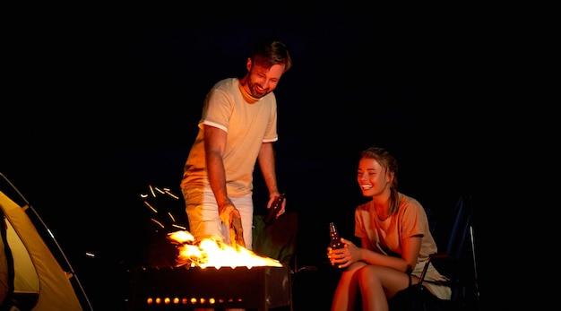 Eine süße frau und ein hübscher mann sitzen auf klappstühlen in der nähe des zeltes am feuer, trinken bier und haben nachts spaß am strand am meer.