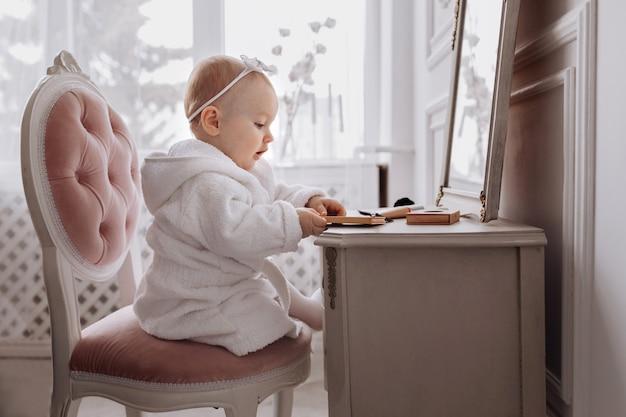 Eine süße kleine frau hält einen make-up-pinsel und hat spaß zu hause. baby girl sitzt auf dem stuhl in der nähe des klassischen spiegels drinnen. kindermode. kleines mädchen fashionista.