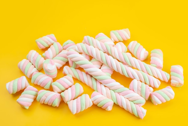 Eine süße marshmallows der vorderansicht lokalisiert auf gelbem schreibtisch, süße zuckerzuckerfarbe