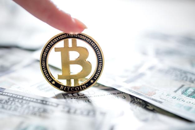 Eine symbolische bitcoin-münze auf banknoten von einhundert dollar. tauschen sie bitcoin-bargeld gegen einen dollar.