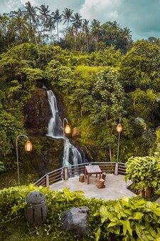 Eine tabelle eines cafés im dschungel mit wasserfall und waldblick auf bali-insel, indonesien