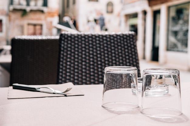 Eine tabelle eines straßen- und sommercafés mit tischbesteck mit einer anlage auf dem tisch.