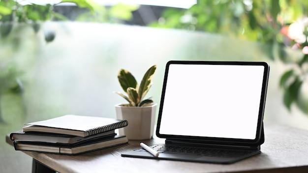 Eine tablette mit einem leeren bildschirm stellt einen weißen holztisch auf