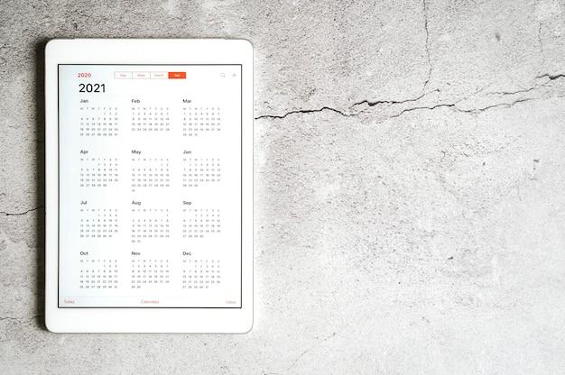 Eine tablette mit einem offenen kalender für 2021 jahre auf einem grau