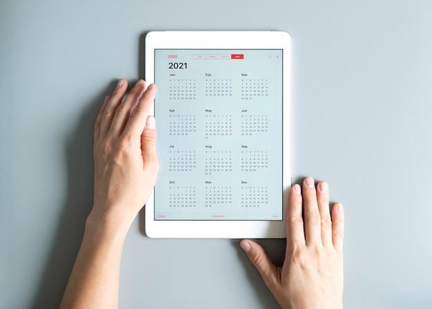 Eine tablette mit einem offenen kalender für 2021 jahre in den händen einer frau