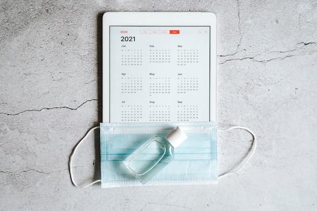 Eine tablette mit einem offenen kalender für 2021 jahre und einer medizinischen schutzmaske und einem händedesinfektionsmittel auf einem grau