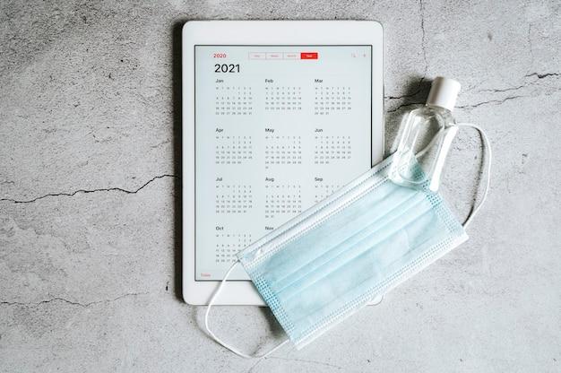 Eine tablette mit einem offenen kalender für 2021 jahre und einer medizinischen schutzmaske