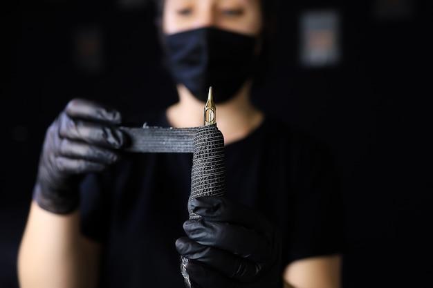 Eine tätowiererin in schwarzen handschuhen hält eine tätowiermaschine vor sich und umwickelt sie zur zusätzlichen fixierung mit einem stretchband