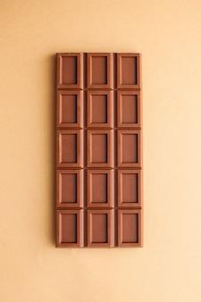 Eine tafel milchschokolade auf einer draufsicht der braunen oberfläche
