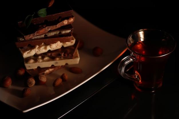 Eine tafel milchschokolade. hausgemachte milchschokolade mit mandeln und getrockneten erdbeeren. stücke von milchschokolade. unbeschriftete milchschokolade. set schokolade mit tee.