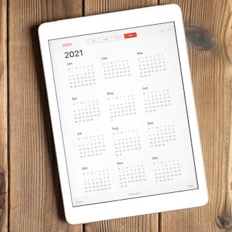 Eine tafel mit einem offenen kalender für 2021 jahre auf einem holzbrettertisch