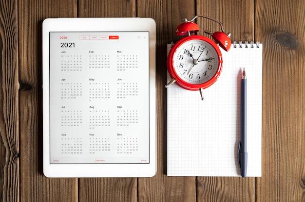 Eine tafel mit einem offenen kalender für 2021 jahre, einem roten wecker und einem frühlingsnotizbuch mit einem stift auf einem holzbretter-tischhintergrund