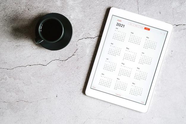 Eine tafel mit einem offenen kalender für 2021 jahre und einer tasse kaffee auf einem grauen betonhintergrund