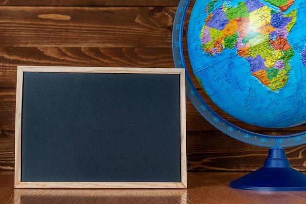 Eine tafel mit platz für text und globus auf holz.