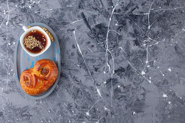 Eine tafel mit süßem verdrehtem gebäck und einer tasse tee auf einem marmorhintergrund.
