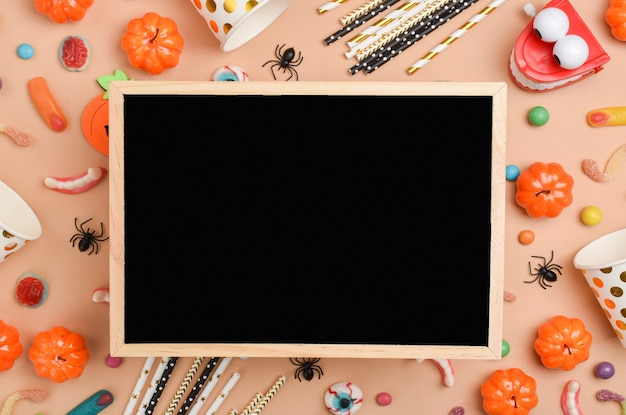 Eine tafel mit verschiedenen süßigkeiten auf orangefarbenem hintergrund mit platz für text. fröhliches halloween. flaches layout, draufsicht, ein ort zum kopieren.