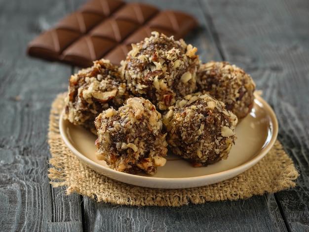 Eine tafel schokolade und kugeln aus nüssen, getrockneten früchten und schokolade auf einem schwarzen tisch. leckere frische hausgemachte süßigkeiten.