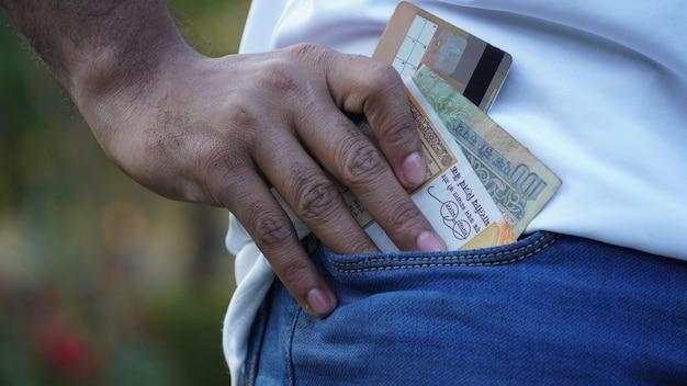 Eine tasche mit etwas indischer währung und bankomatkarte