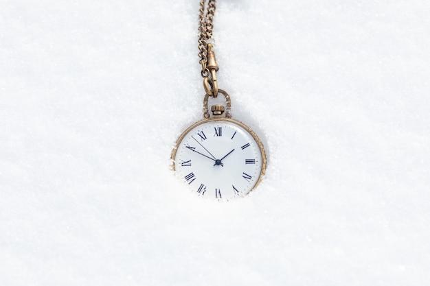 Eine taschenuhr im schnee. das konzept der verstrichenen zeit