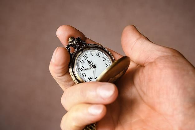 Eine taschenuhr in den händen eines mannes