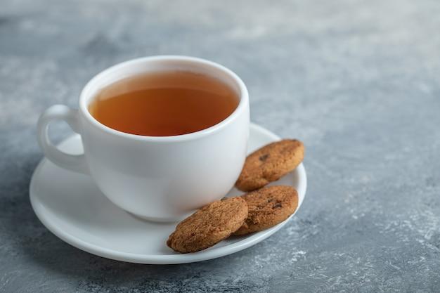 Eine tasse aroma-tee mit leckeren keksen.
