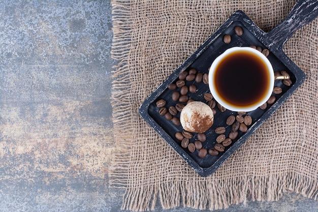 Eine tasse aromakaffee mit kaffeebohnen auf dunklem brett