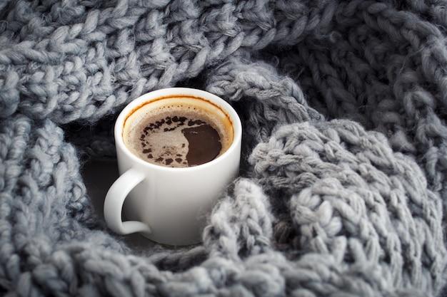 Eine tasse aromatischer kaffee in wolle verpackt