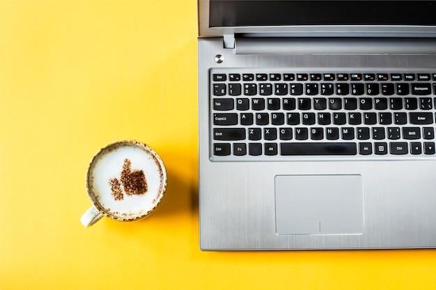 Eine tasse cappuccino, auf der ein lächeln wie ein daumen hochgezogen wird
