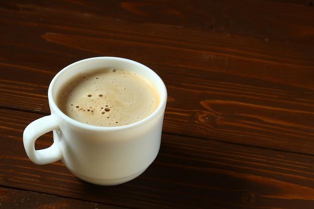 Eine tasse cappuccino auf einem holz