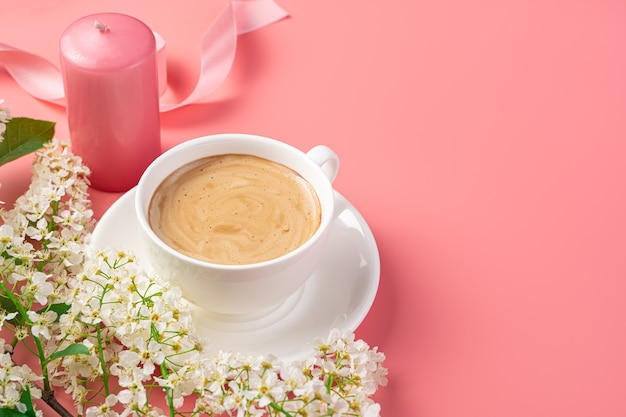 Eine tasse cappuccino, blumen, eine kerze und ein band auf einem zartrosa hintergrund. seitenansicht, kopienraum. glückwunsch-grußkarte.