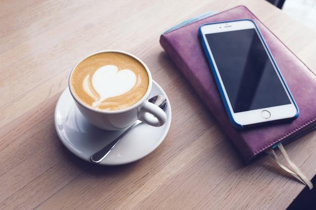 Eine tasse cappuccino, ein notizbuch und ein telefon stehen auf einem holztisch im café.